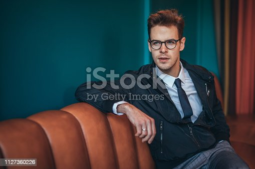 Stylish, handsome businessman with eyeglasses sitting on orange sofa.
