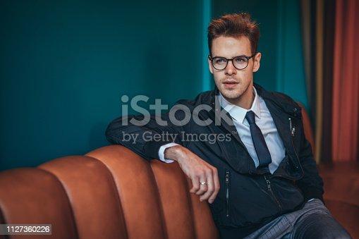 Stylish, handsome businessman with eyeglasses sitting on orange sofa.