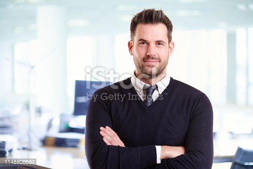 istock Casual businessman portrait while standing in the office with folded arms 1148808852