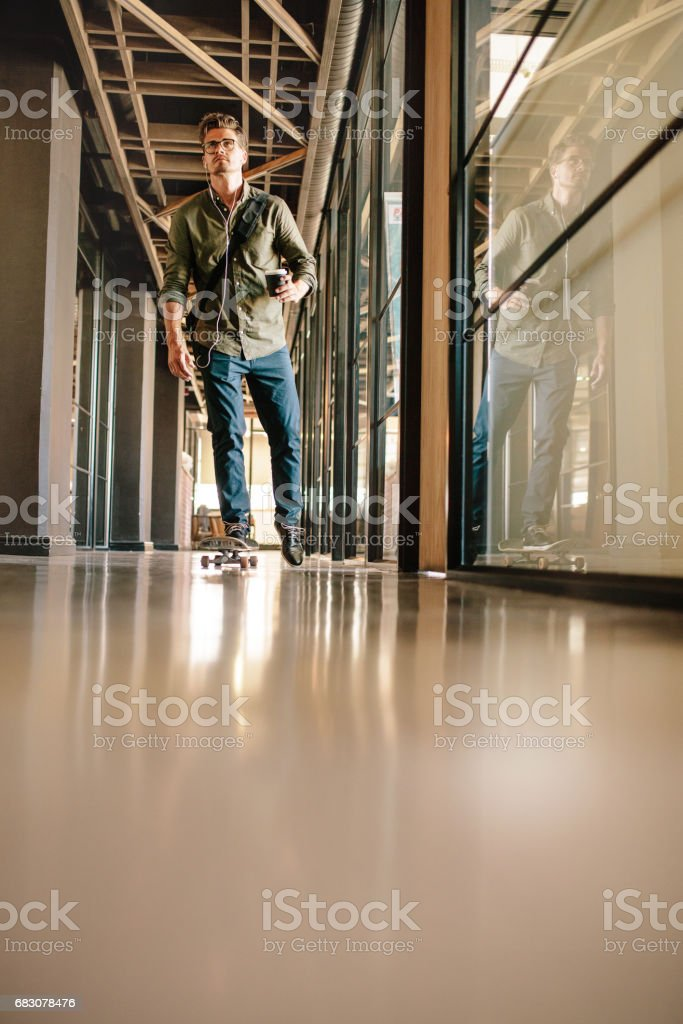 Casual businessman skating through office corridor foto de stock royalty-free