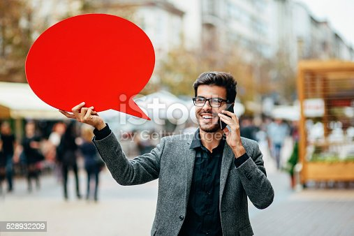istock Casual businessman with phone and red speech bubble outdoors 528932209