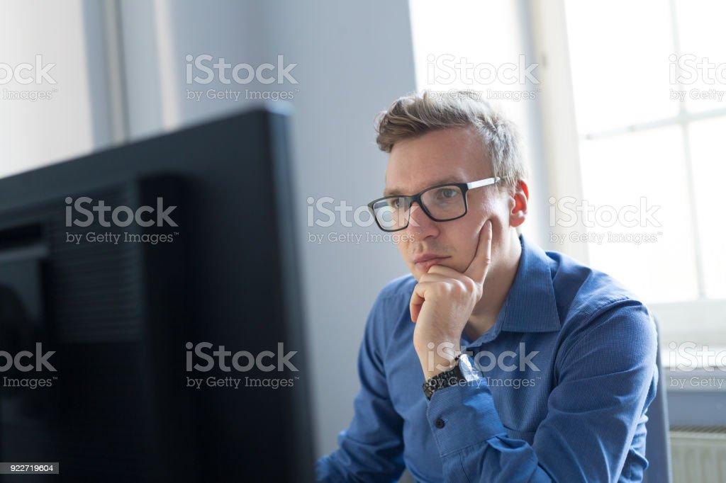 Lässige Geschäftsmann arbeiten im Büro, am Schreibtisch sitzen, tippen auf Tastatur, Computer-Bildschirm betrachten. – Foto