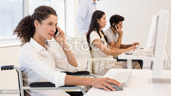 istock Casual businesswoman in wheelchair on the phone 692244110