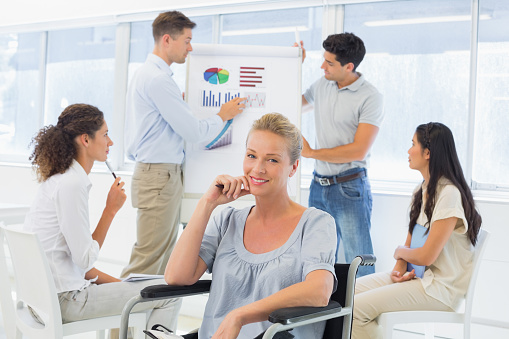 660681964 istock photo Casual businesswoman in wheelchair smiling at camera during presentation 842044306