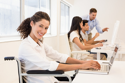 660681964 istock photo Casual businesswoman in wheelchair smiling at camera 692244272