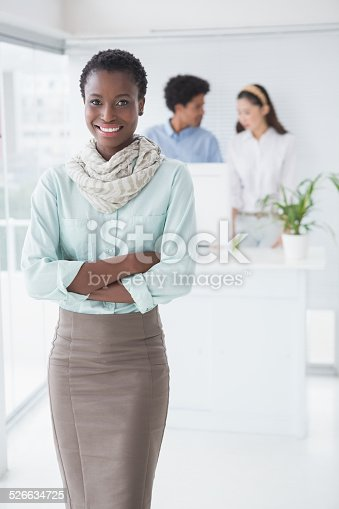 Casual businesswoman smiling at camera in creative office