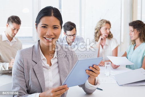 1150572102istockphoto Casual businesswoman using her tablet during a meeting 842016156