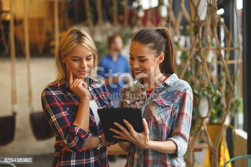 Two young casual businesswomen are discussing  market research statistics using digital tablet during business meeting. There are people in the background cooperating.