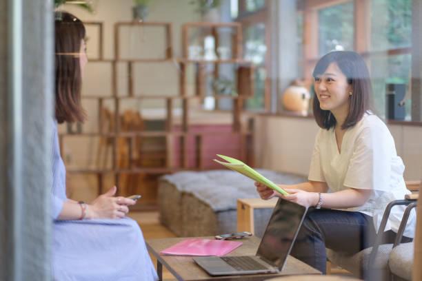 カフェで話をビジネスを持つカジュアルなビジネスウーマン - スマートカジュアル ストックフォトと画像