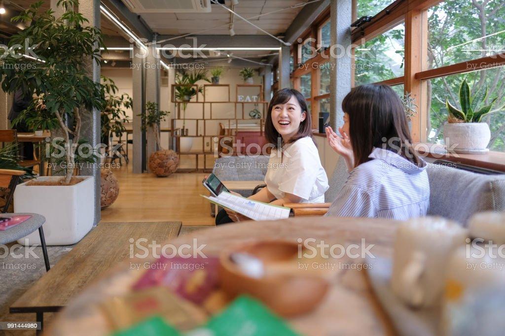 カフェで話をビジネスを持つカジュアルなビジネスウーマン ストックフォト