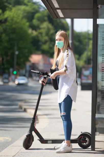 メトロ都市バスを待っている現代の折りたたみ式都市電動スクーターとコロナウイルスの拡散に対するカジュアルな白人ティーンエイジャーのウェーリング保護フェイスマスク。都市モビリ� - sustainability ストックフォトと画像