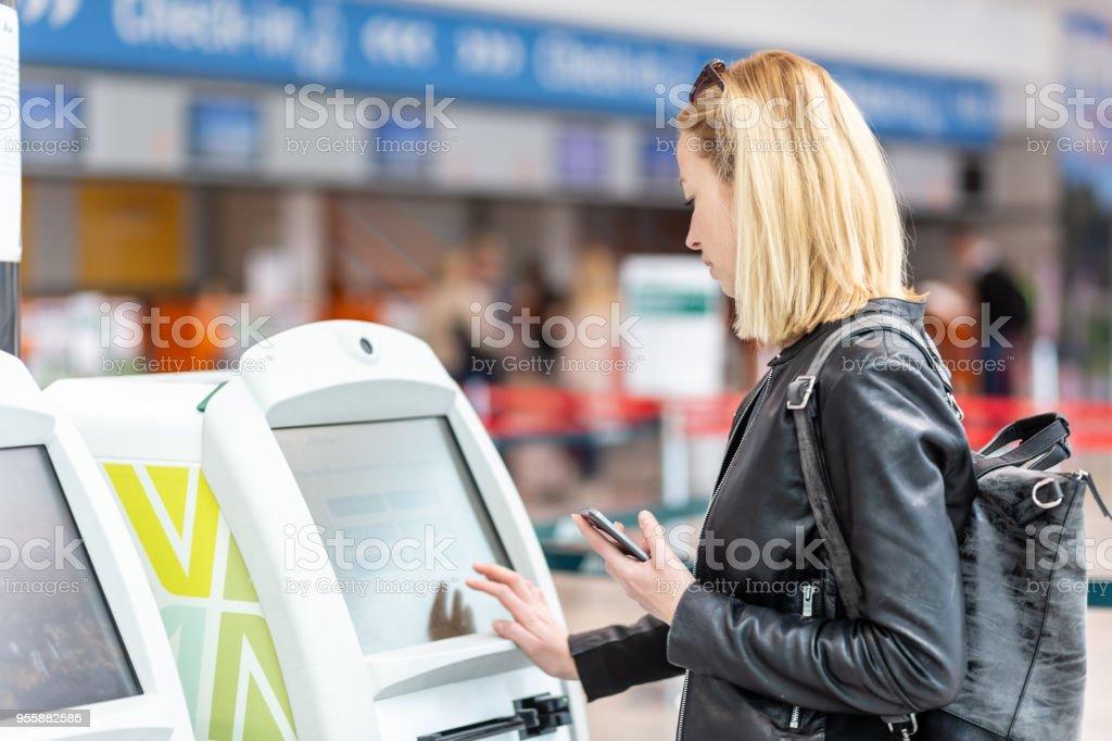 Lässige kaukasischen Frau mit Smartphone-APP und Check-in-Automaten am Flughafen immer die Bordkarte. – Foto