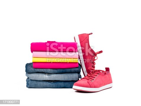 Multicolored casual clothes folded in pile with a pair of canvas shoes on white background
