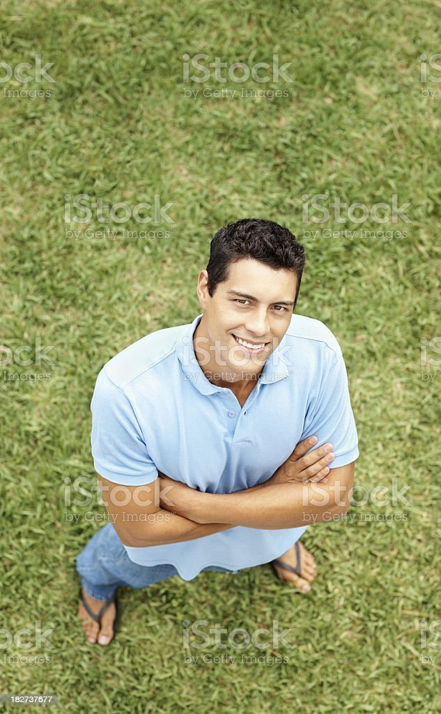 Casual confident guy standing on grass with hands folded royalty-free stock photo