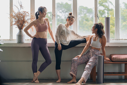 Young adult yoga practitioners have a casual conversation during warm up for a yoga session