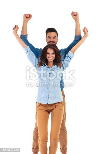 854381886 istock photo casual couple celebrating success with hands in the air 854377338