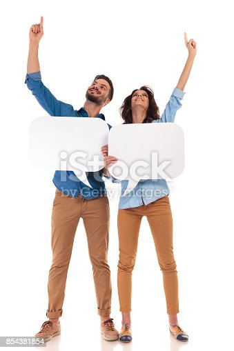 854381780istockphoto casual couple hoding speech bubbles and ponting up 854381854
