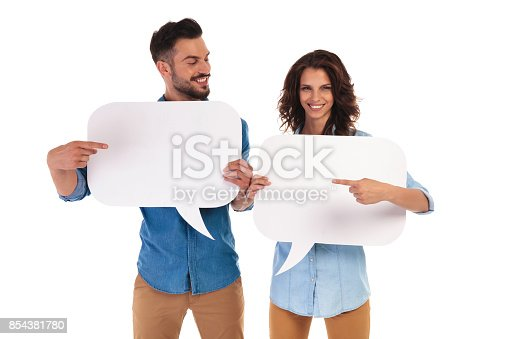 istock casual couple holding speech bubbles pointing to each other 854381780