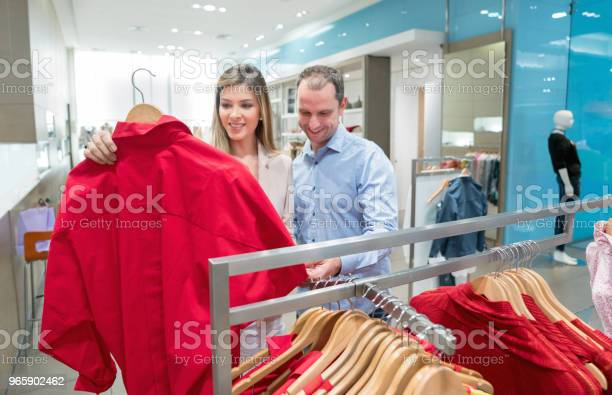 Casual Couple Shopping For Clothes At A Store Stock Photo - Download Image Now