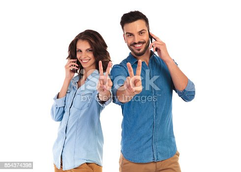 854381780istockphoto casual couple speaking on their phones make the victory sign 854374398