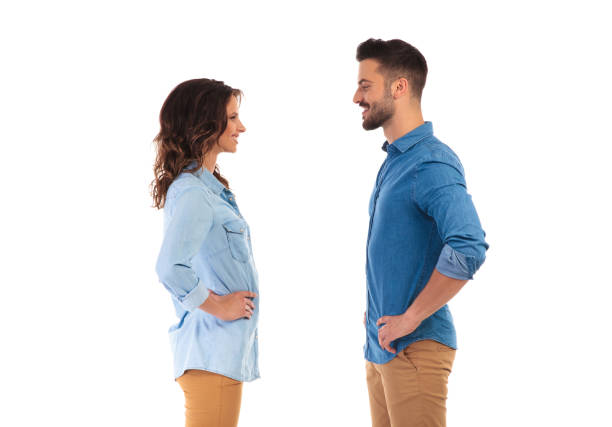 casual couple standing with hands on waist facing each other stock photo