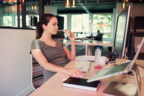 Casual creative freelancer woman eating a sandwich in office stock photo