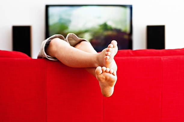 legere schneidersitz junge spielt auf roten sofa - kids tv zimmer stock-fotos und bilder