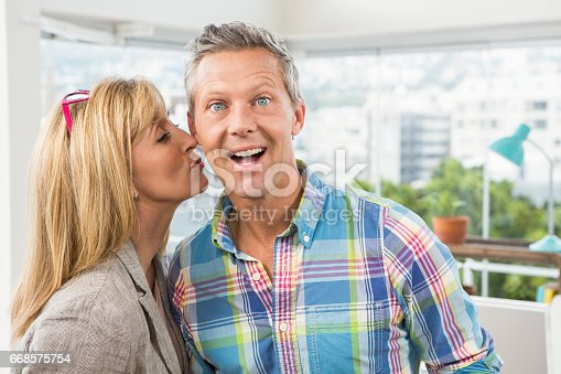 919520858 istock photo Casual designer giving her colleague kiss on cheek 668575754