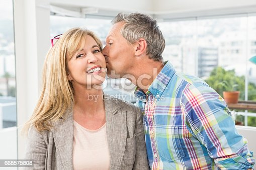 istock Casual designer giving his colleague kiss on cheek 668575808