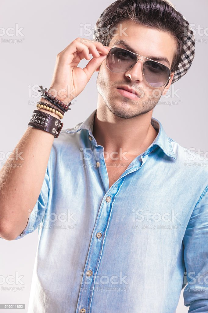 Casual fashion man taking off his sunglasses stock photo