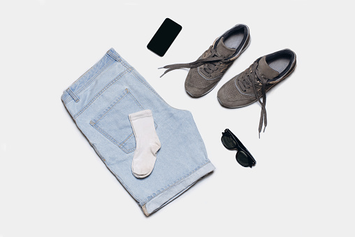 Casual fashionable clothes and accessories on a white background. Denim shorts, sneakers, socks, sunglasses, phone. Flat lay, top view.