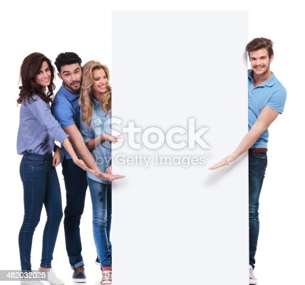 istock casual friends pointing and showing you a blank banner 482032025