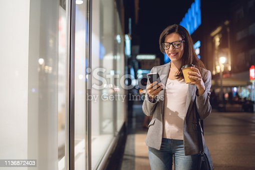 istock Casual girl typing on the mobile phone while walking the street 1136872403