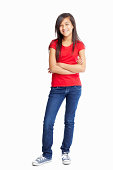 Full length of a casual girl with hands folded against white background - copyspace