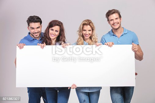 istock casual group of young people holding a big blank board 521382327