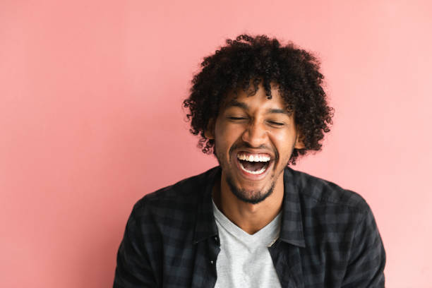Casual guy Casually dressed African-American guy posing in front of pink background. afro caribbean ethnicity stock pictures, royalty-free photos & images