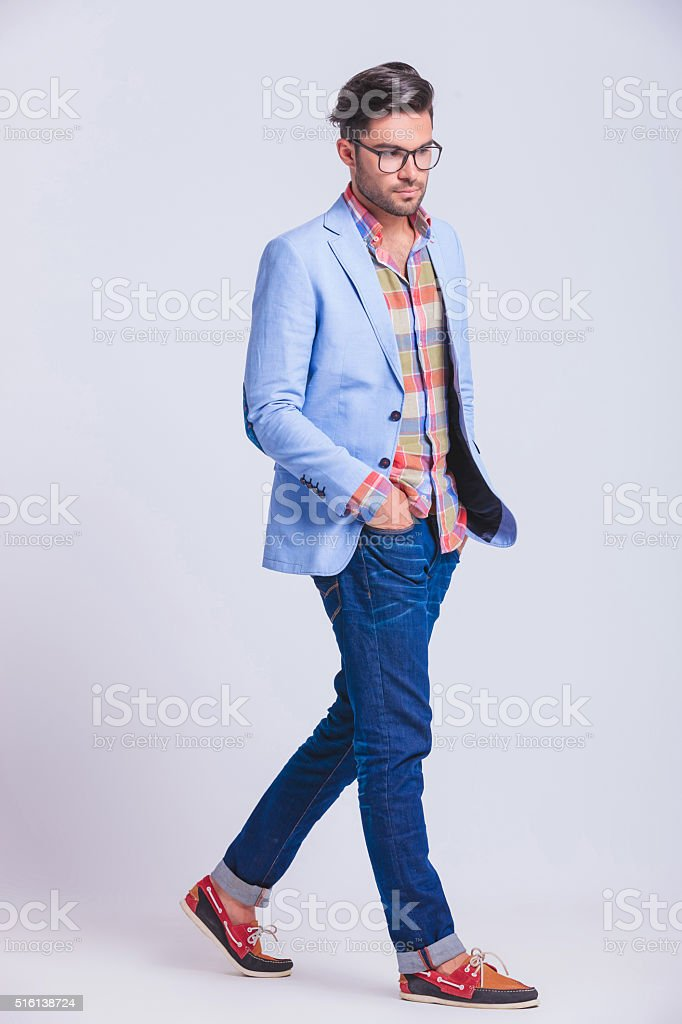 casual guy walking in studio background with hands in pockets stock photo