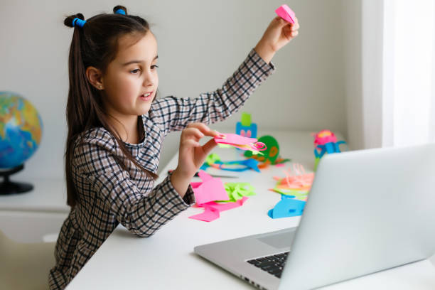 casual indoor portrait of child girl with laptop, portrait of young child girl crafting at home stock photo