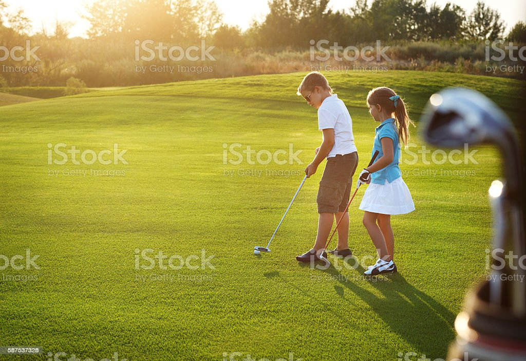 Casual kids at a golf field holding clubs stock photo