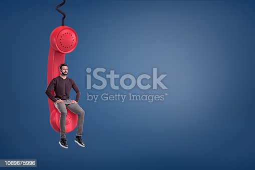 A casual looking bearded man sits on a giant red retro phone receiver hanging from a cord. Call center worker. Waiting for important call. Priority message.