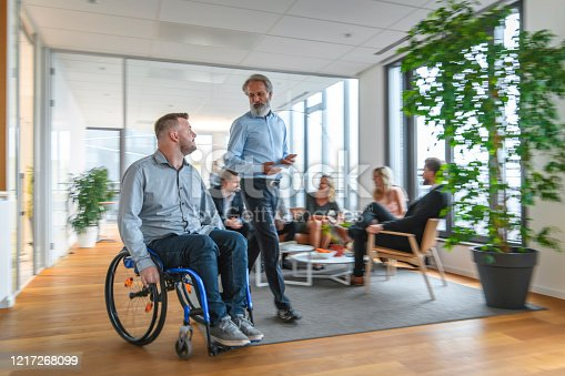 Junior businessman in wheelchair conversing with mature male colleague while moving through office lobby.