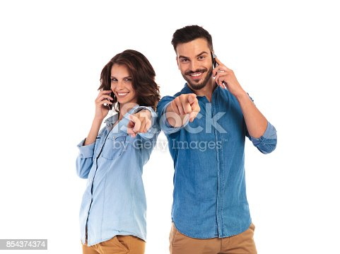 854381780istockphoto casual man and woman talking on their phones are pointing 854374374