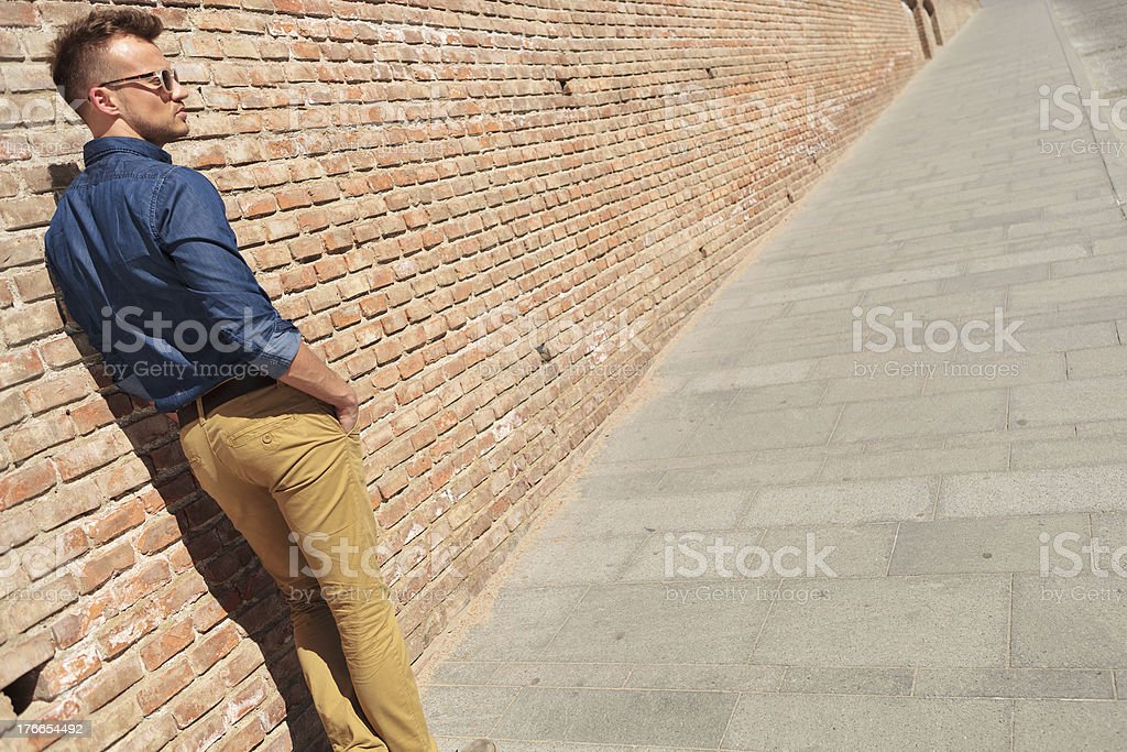 casual man by wall with hands in pockets royalty-free stock photo