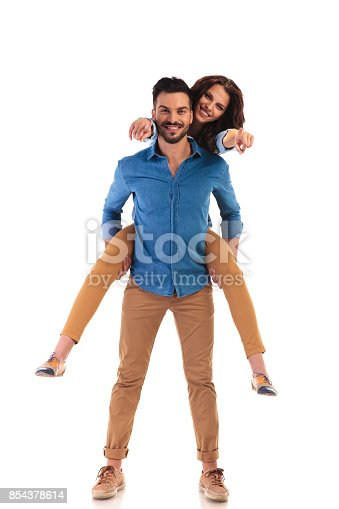 854381886istockphoto casual man carrying his woman while she is pointing 854378614