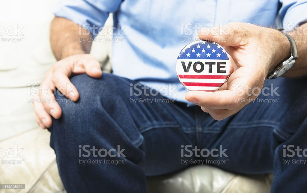 Casual man holding a vote button for the election stock photo