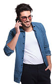 Attractive young casual man holding his hand in pocket while talking on the phone.