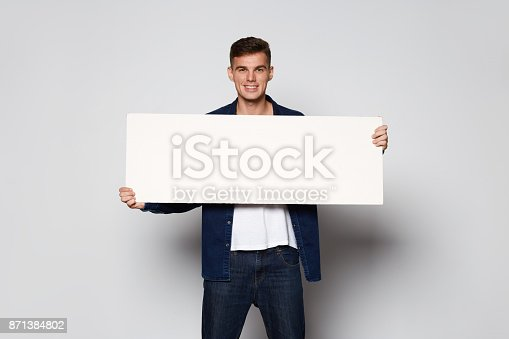istock Casual Man holding white papper card on white background 871384802