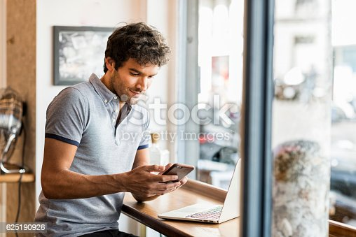 Young male working in coffee bar on laptop. Texting message on his smart phone