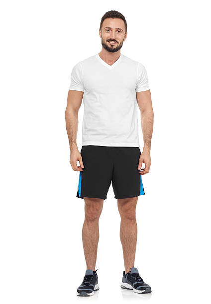 Casual man in sport clothing Cheerful man in white t-shirt looking at camera shorts stock pictures, royalty-free photos & images
