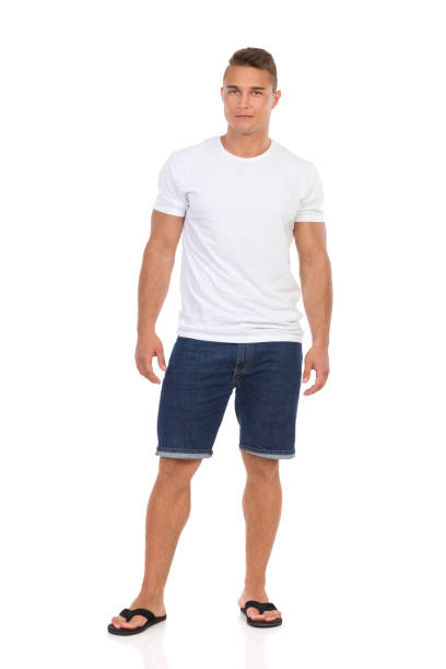 Casual Man In White T-shirt And Jeans Shorts Looking At Camera Handsome young man in white shirt, jeans shorts and black sandals is standing and looking at camera. Front view. Full length studio shot isolated on white. shorts stock pictures, royalty-free photos & images